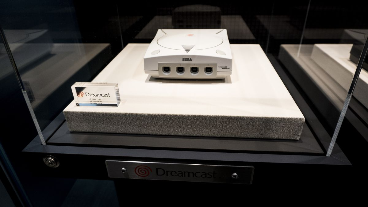 A Dreamcast sits inside a glass case, looking like a museum exhibit