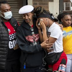 Zaniya Cribbs, niece of Verndell Smith, is comforted by family and friends after speaking to reporters at Ultimate Threat Dance Organization's studio, Thursday, May 20, 2021. Verndell, the founder of the dance studio was shot and killed yesterday.