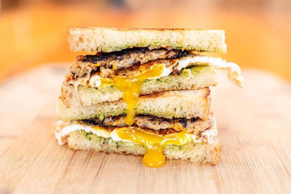 Two egg sandwiches sit on top of each other with a crisp sausage patty and green pesto