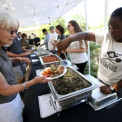 Angeline Tuyisabe, right, serves Connie Castleton lunch at the Real Food Rising farm in Salt Lake City on Wednesday, July 13, 2016.