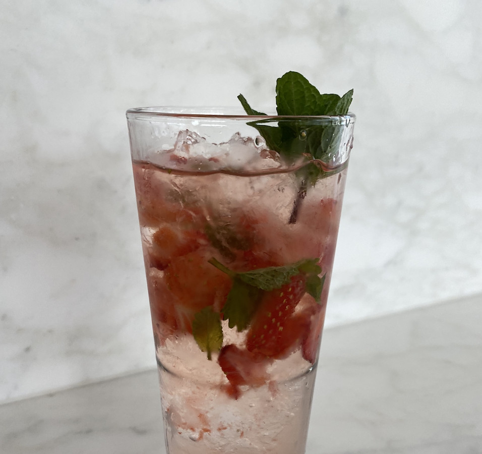 A clear drink is filled with muddled strawberries and topped with a mint sprig.