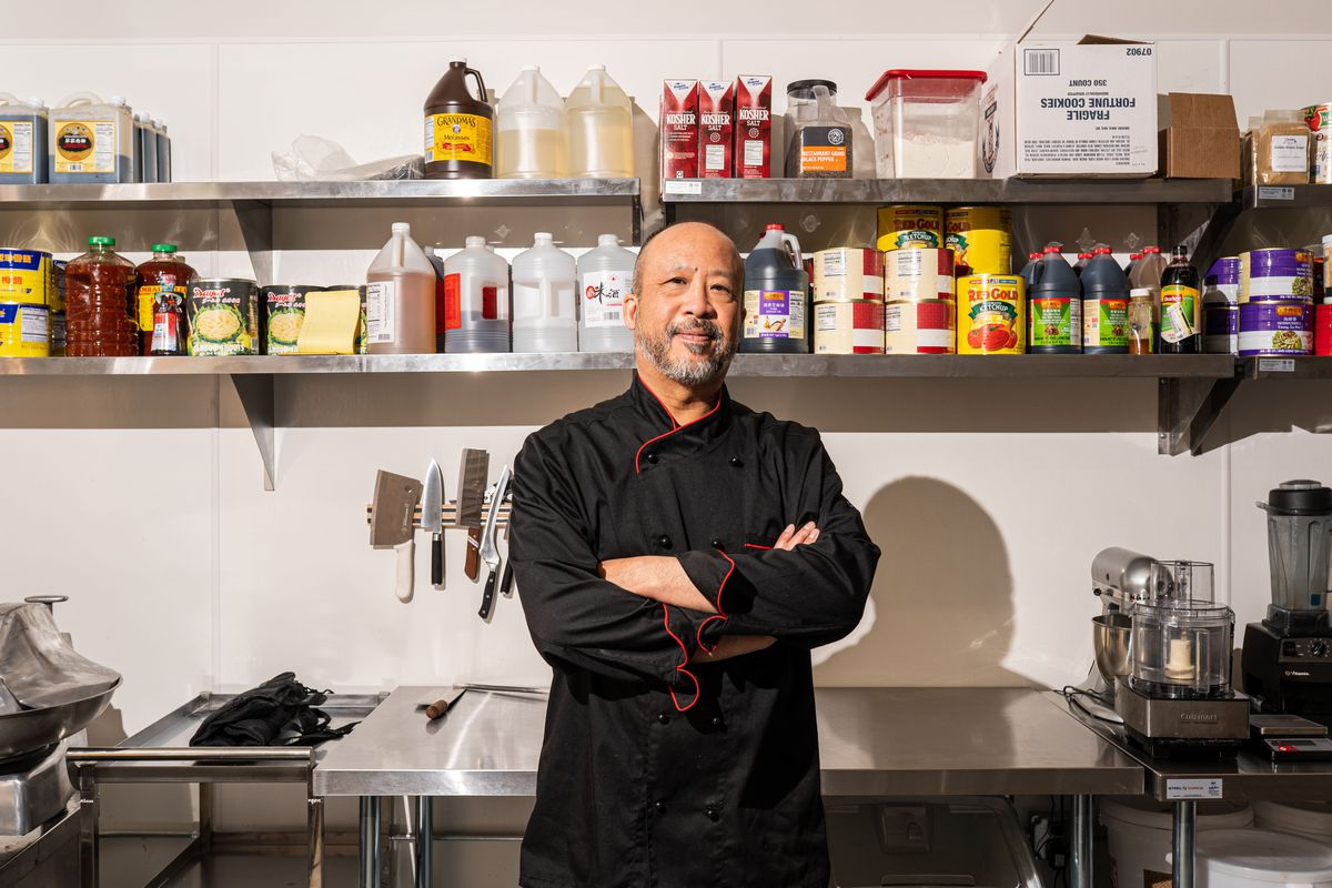 Steven Chin, the owner of YaYa, standing in a stainless-steel-lined kitchen. Behind him are jars of soy sauce, black vinegar, mustard powder, and hoisin.