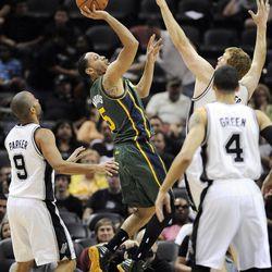 Utah Jazz's Devin Harris, center, shoots between San Antonio Spurs' Tony Parker (9), of France, Danny Green (4) and Matt Bonner during the second half of an NBA basketball game, Sunday, April 8, 2012, in San Antonio.