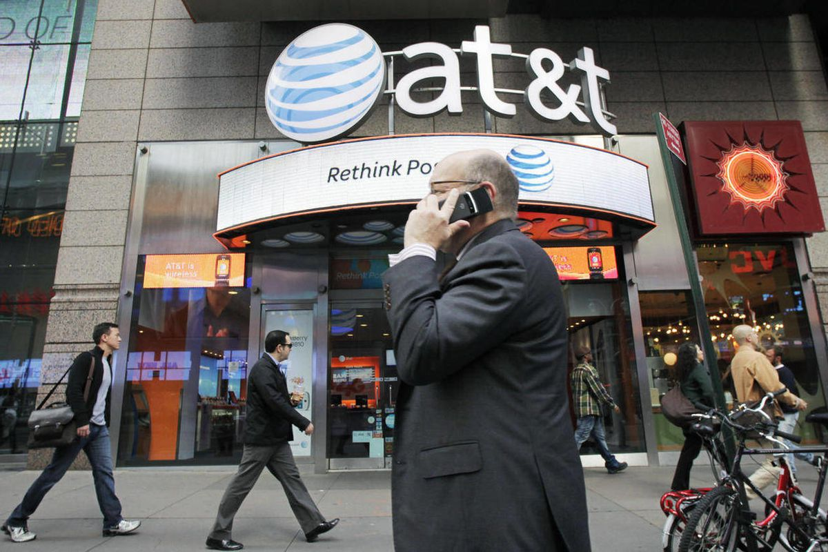 FILE - In this Oct. 18, 2011 file photo, a man using a cell phone passes an AT&T store, in New York.   AT&T is gaining new wireless subscribers at the lowest rate in eight years, as the number of people joining the network through resellers and non-phone