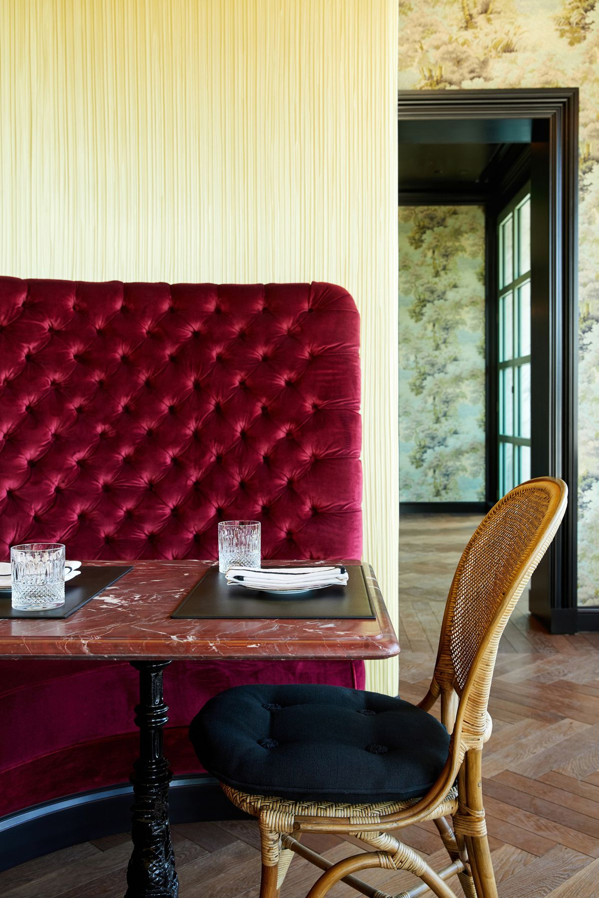 Table with wicker chair and platemat at Gucci Osteria.