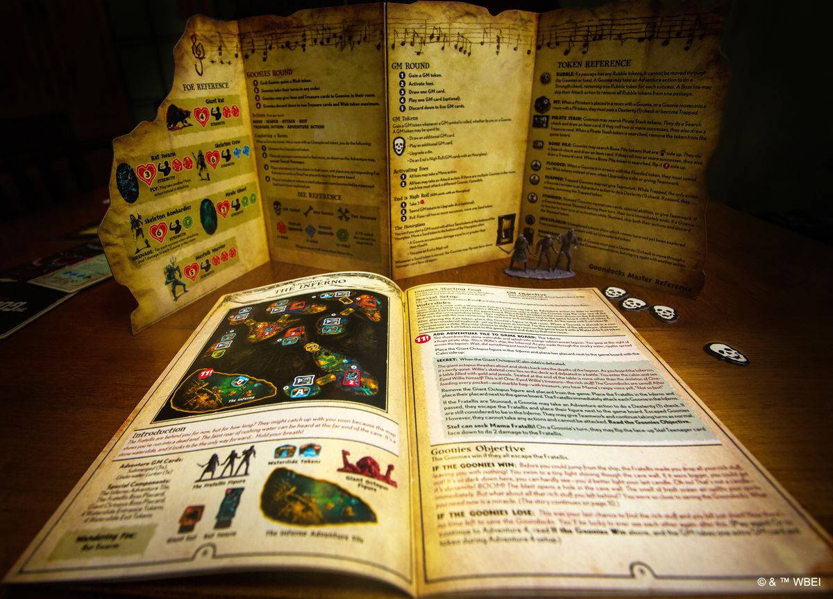The game master book, plus a screen to hid the action from players. A pile of skull tokens sits on the table next to a miniature of the entire evil family from the movie.