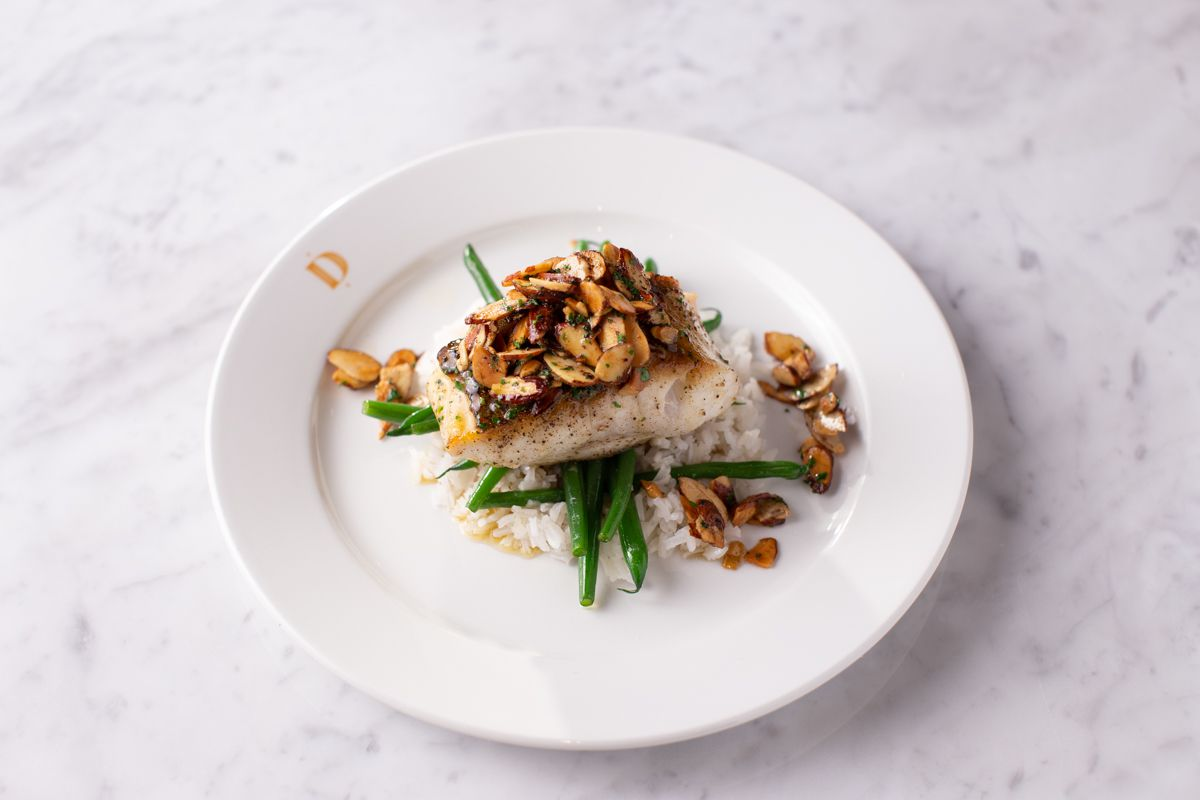 A pice of rockfish covered in almonds sits on top of green beans and white rice at Dauphine's