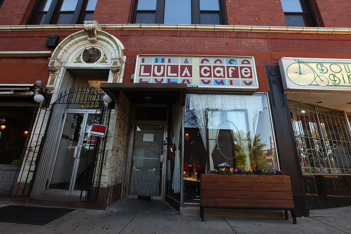"""A storefront inside a brick building from the street. White curtains are visible through a large window and a sign overhead reads """"Lula Cafe."""""""
