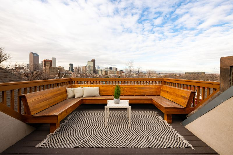 A rooftop deck with a view of skyscrapers in the distance features a built-in wooden bench for seating.