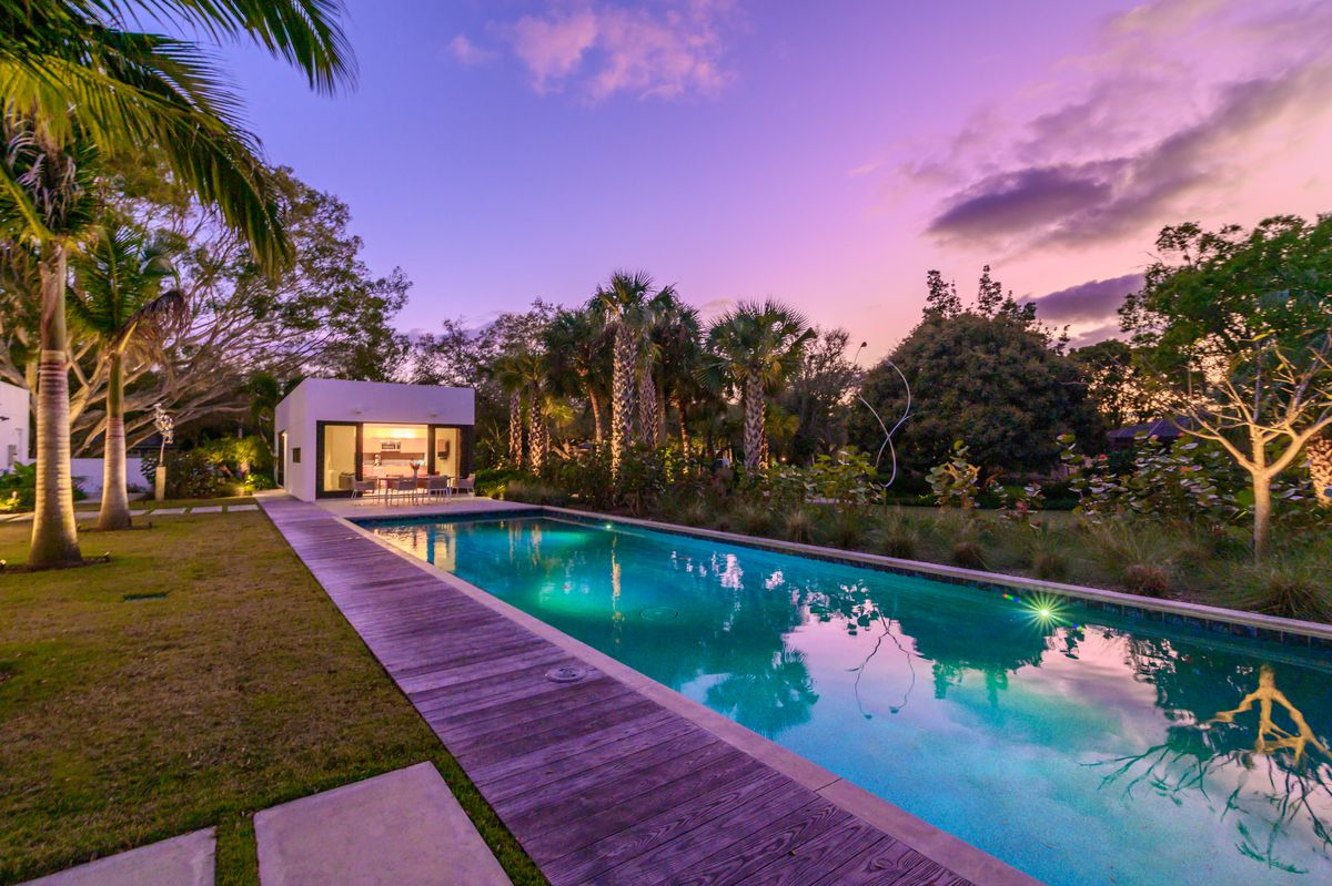 A long lap pool at dusk has a white boxy guest house at one end of the pool.