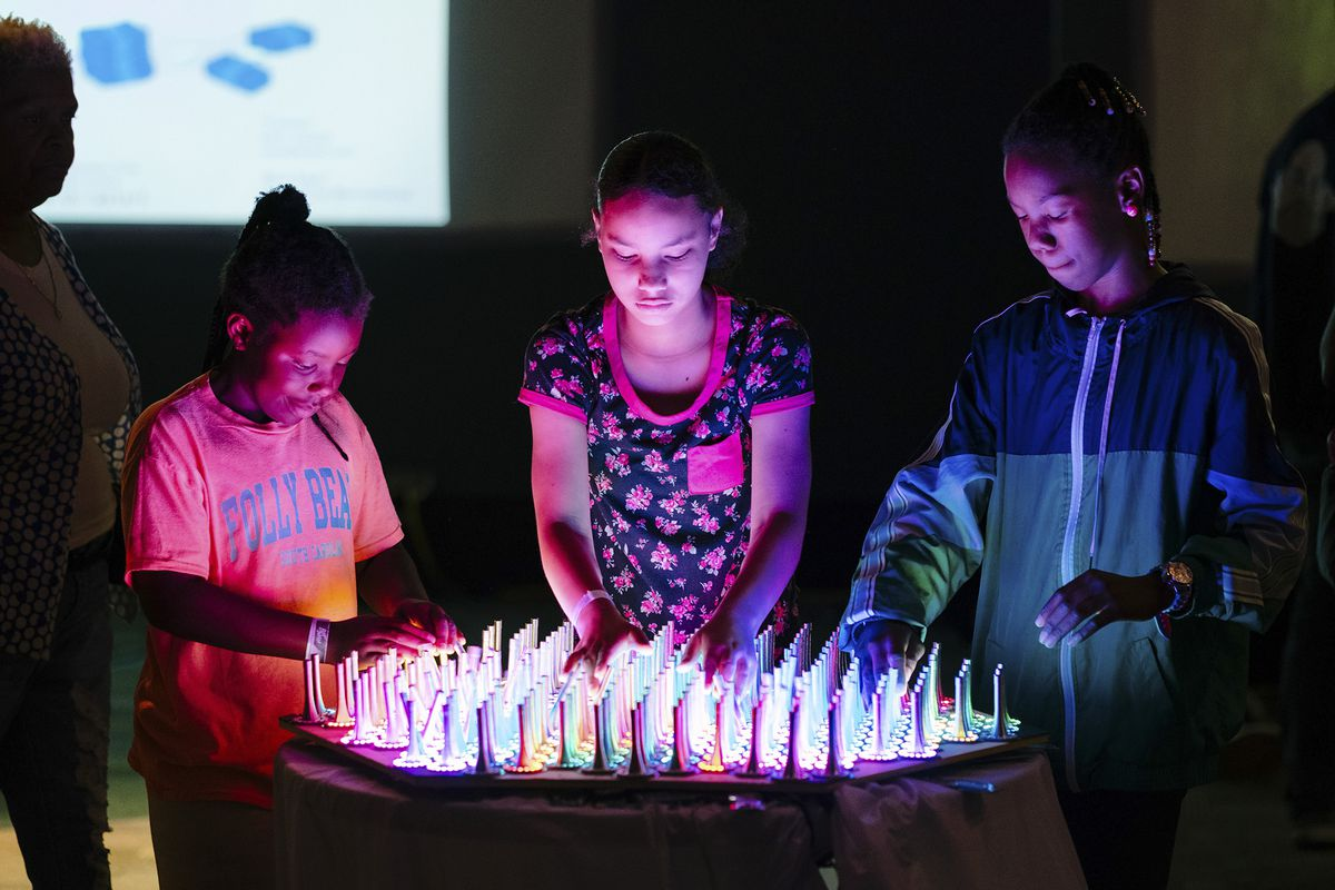 Three visitors to Bit Bash 2019 at the Museum of Science and Industry in Chicago stand in a dark room around a plywood table covered with springs that look like doorstops. Rainbow LEDs glow inside the installation, reacting to their movements.