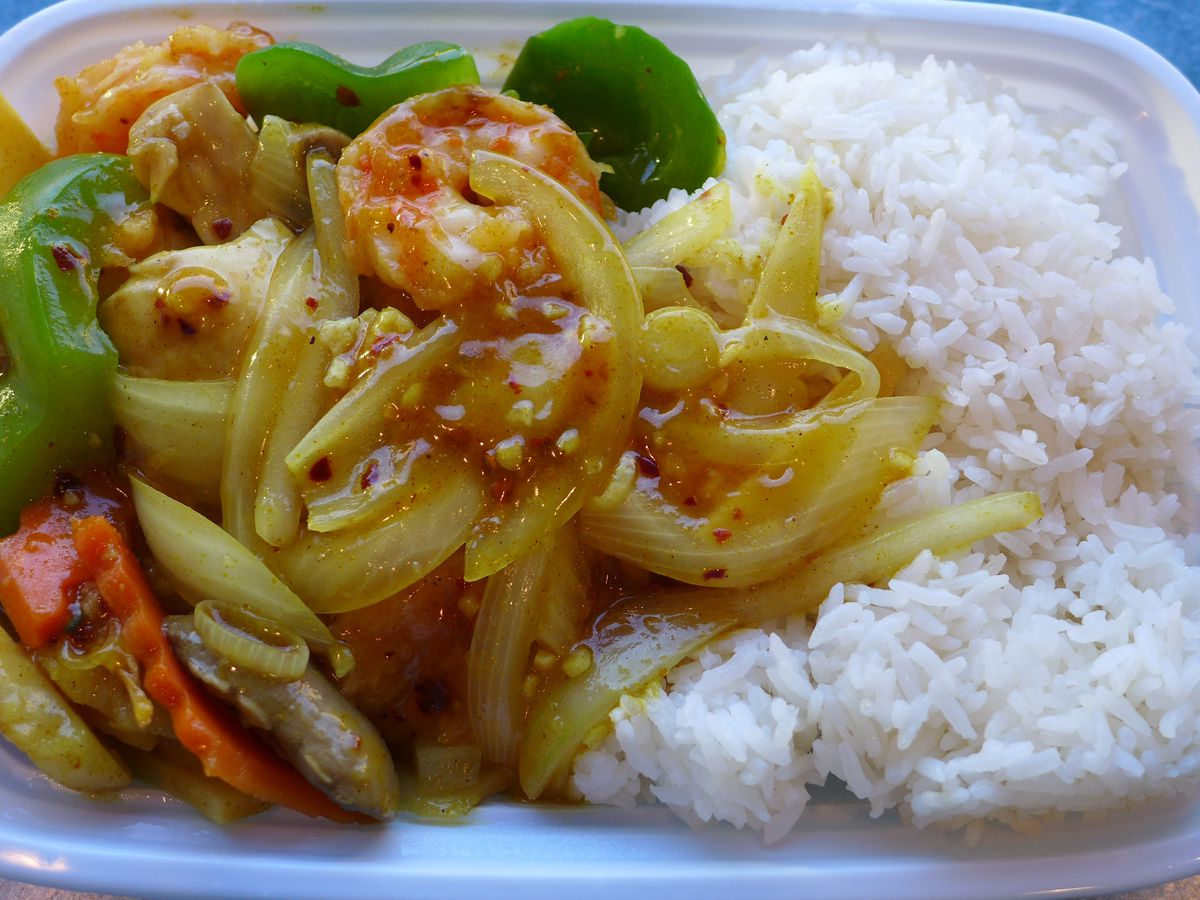 A shrimp stir fry with plenty of veggies in a white plastic container.