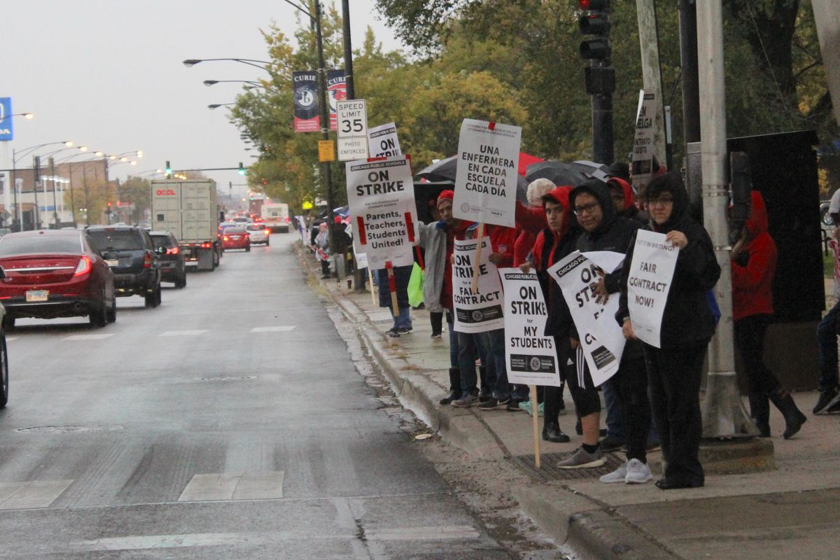 Striking Chicago teachers hold signs in front of Curie Metropolitan High School at the start of a lengthy picket line down Pulaski Road. Rain in the forecast leads some passersby to drop off ponchos.