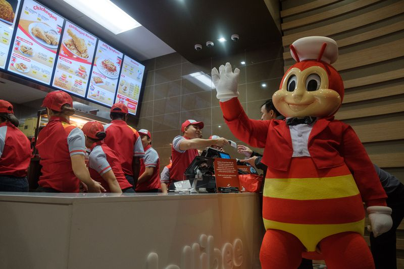 Jollibee, the mascot after which the franchise is named, hangs out at the counter.