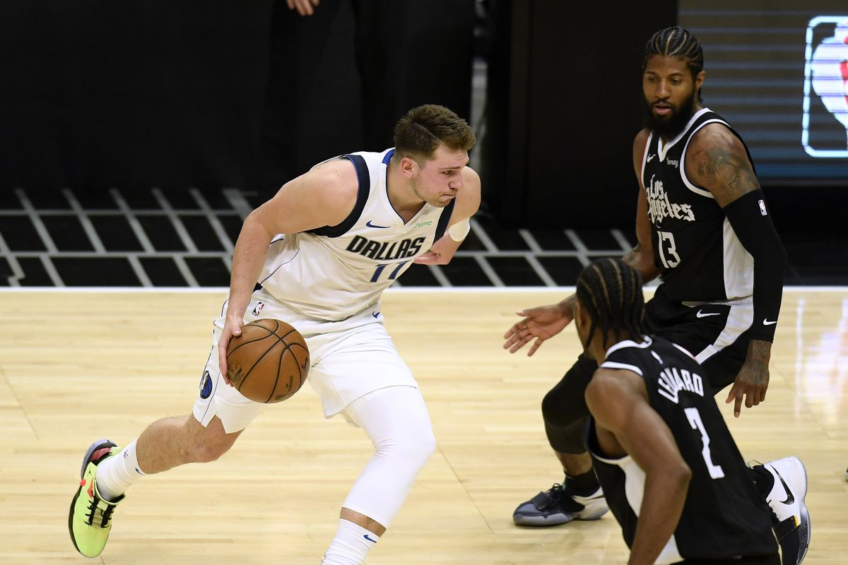 Luka Doncic #77 of the Dallas Mavericks drives between Paul George #13 and Kawhi Leonard #2 of the LA Clippers in the second quarter during game one of the Western Conference first round series at Staples Center on May 22, 2021 in Los Angeles, California.