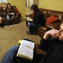 Kit Hunt, center, reads a passage from The Book of Mormon as her husband Clayton, front, along with daughter Aspen (15) and son Christian (13) follow along in their home in Bountiful on Thursday, Dec. 26, 2013.
