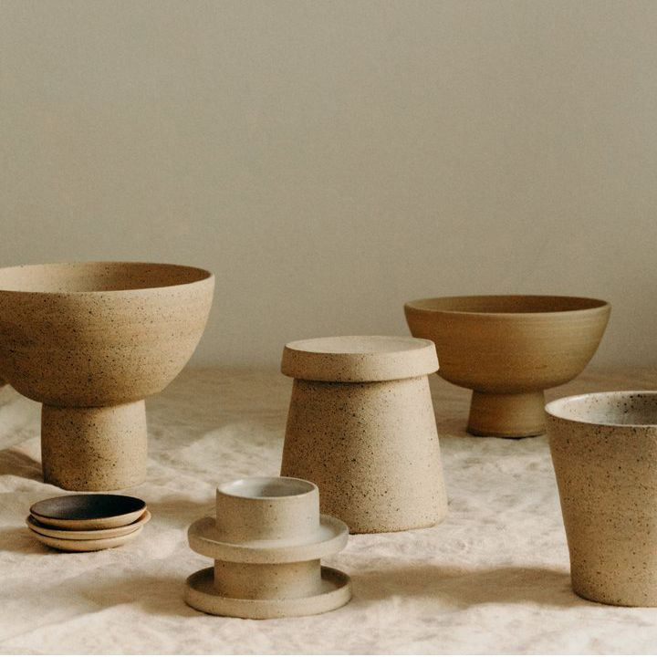 A collection of six ceramic vases sit on top of a light brown table.
