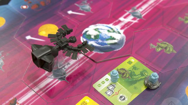 A miniature representing the Black Angel colony ship sails on towards the cardboard tile representing the Earth-like world of Spes. A planet in the foreground has been visited by tiny robots, agents of one of the game's four competing AI.