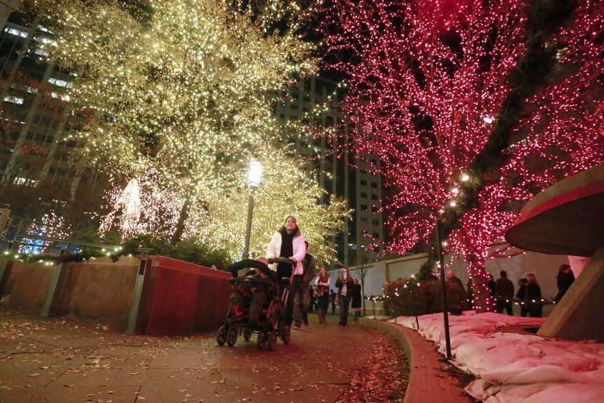 Pedestrians check out the new lights on the trees at the Temple Square Friday, Nov. 28, 2014, in Salt Lake City.