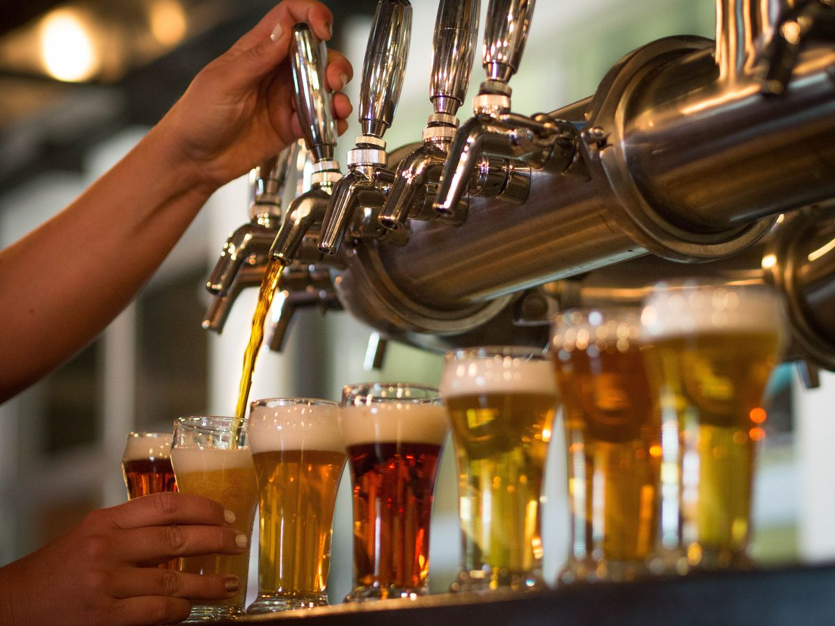 A tap pouring beer into a lager class with a flight of beer in the background.
