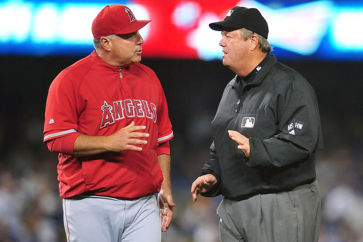 June 12, 2012; Los Angeles, CA, USA; Los Angeles Angels manager Mike Scioscia (14) argues a call to umpire Joe West in the eighth inning at Dodger Stadium.  Mandatory Credit: Gary A. Vasquez-US PRESSWIRE