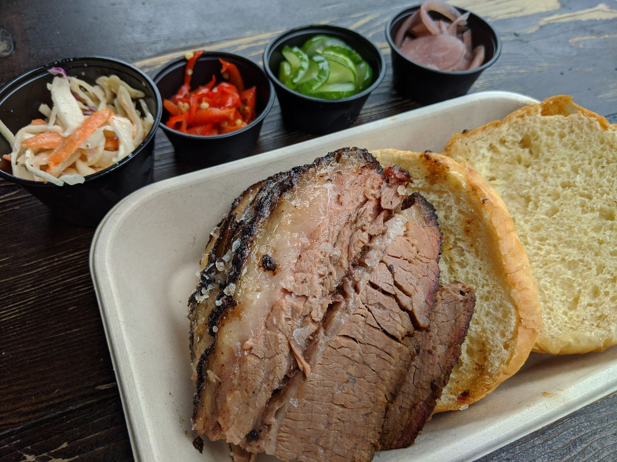 Sliced brisket on a roll with little black plastic cups of pickled vegetables in the background.