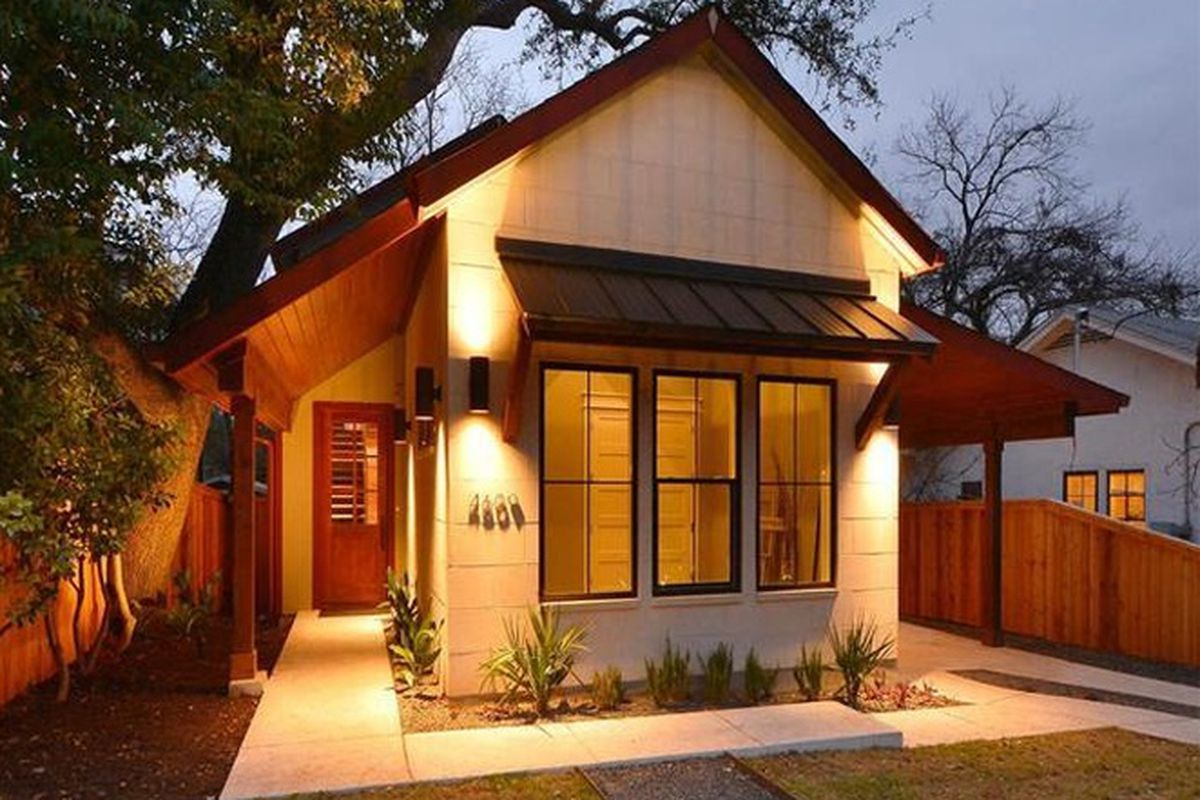 traditional looking frame house at dusk with landscape lighting