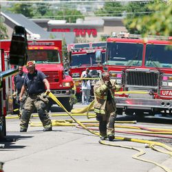 Unified Fire Authority firefighters begin laying out their hoses for storage after fighting a fire at 3381 S. 3170 East in Millcreek on Sunday, July 5, 2020.