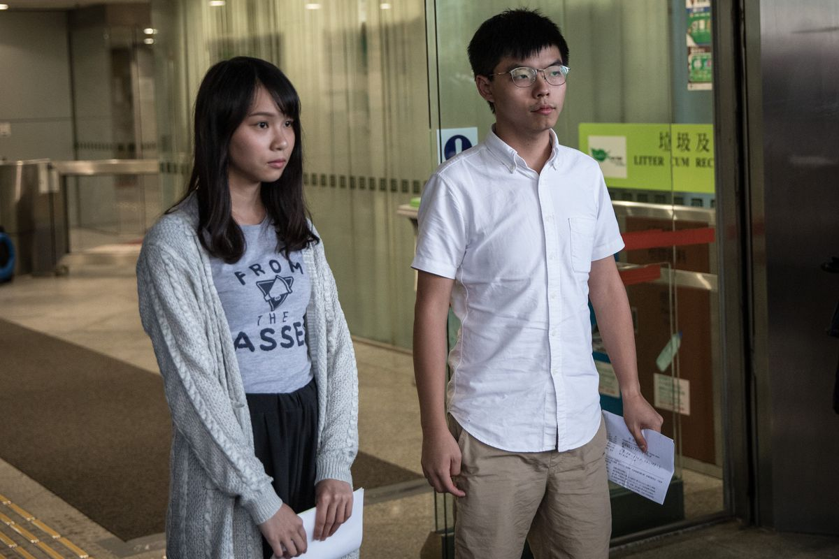 Agnes Chow and Joshua Wong, two pro-democracy Hong Kong protesters, walk toward a press conference after being arrested and released on bail.