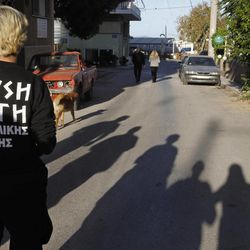 """In this Thursday, April 26, 2012 photo members of extreme far-right Golden Dawn party walk on the street as part of an election campaign in the suburban town of Artemis, 25 kilometers (15 miles) east of Athens. Reeling from a vicious financial crisis that has cost them pensions and jobs, Greeks have been turning away in droves from the mainstream politicians they feel have let them down. Firmly on the fringe of the right since it first appeared 20 years ago, Golden Dawn garnered a meager 0.23 percent in the 2009 elections. But its popularity has shot up over the past few months and support stood at about 5 percent in recent opinion polls, well above the 3 percent threshold needed to enter parliament. Writing on shirt reads: """"Golden Dawn, eastern Attica""""."""