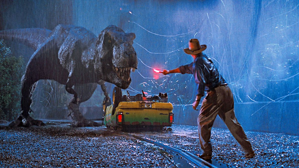 Alan Grant (Sam Neill) waves a lit emergency flare to distract an oncoming Tyrannosaurus Rex.