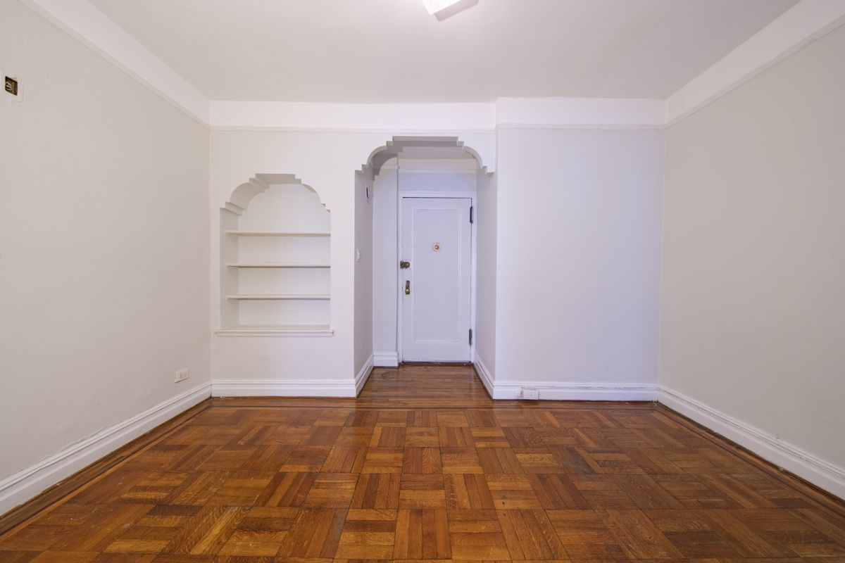 A living room area with hardwood floors, an arched entrance, and light grey walls.