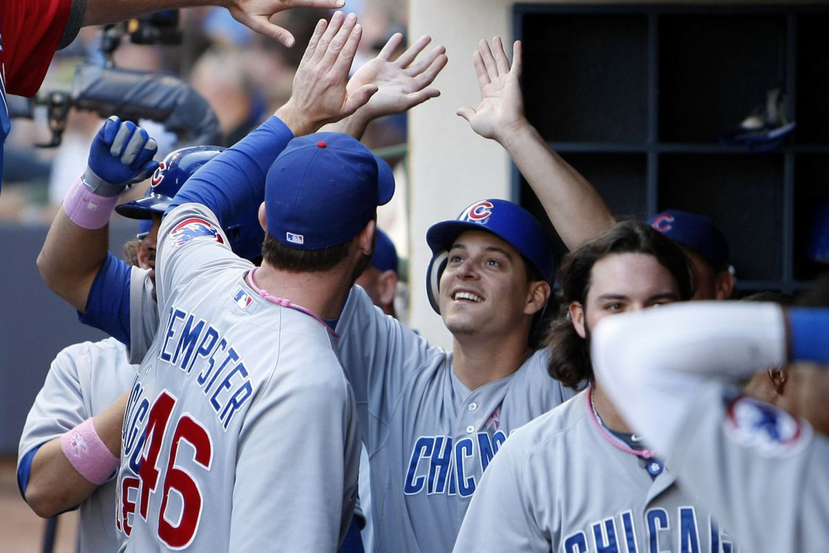 Bryan LaHair of the Chicago Cubs celebrates in the dugout after arriving home safely against the Milwaukee Brewers at Miller Park in Milwaukee, Wisconsin. (Photo by Mike McGinnis/Getty Images)