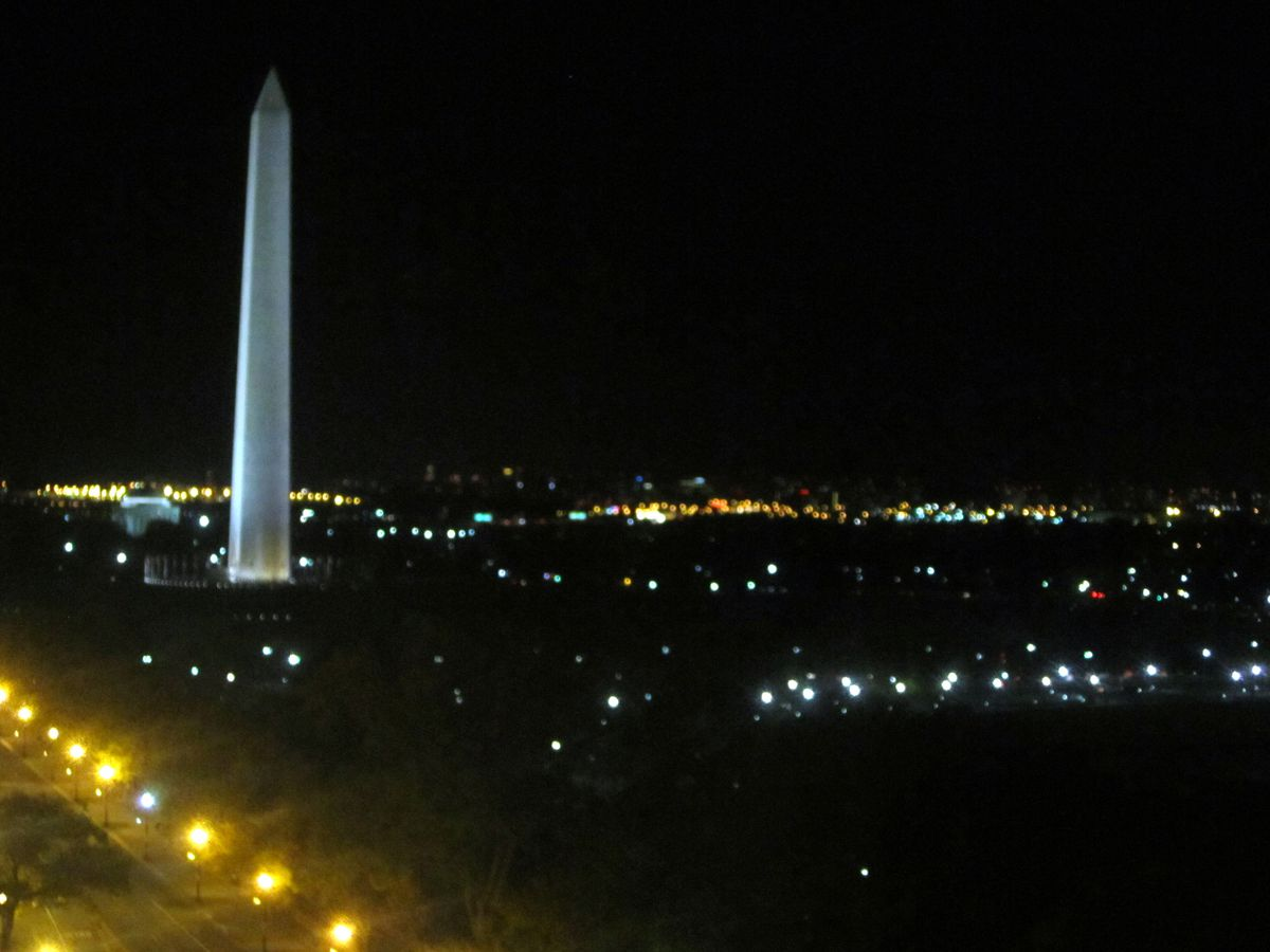 A rooftop is in the foreground. In the distance is the cityscape of Washington D.C. and the Washington monument at night.