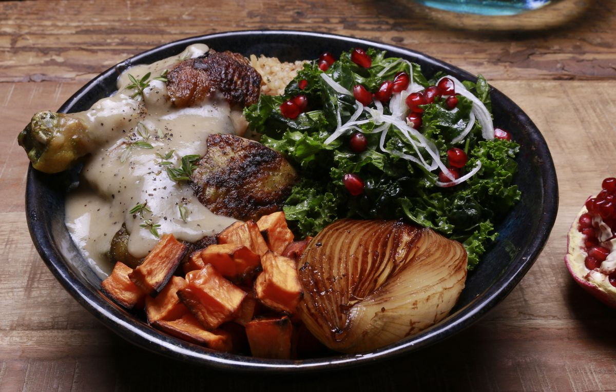 A bowl of chicken with gravy, sweet potato, balsamic onion, kale, pomegranate seeds.
