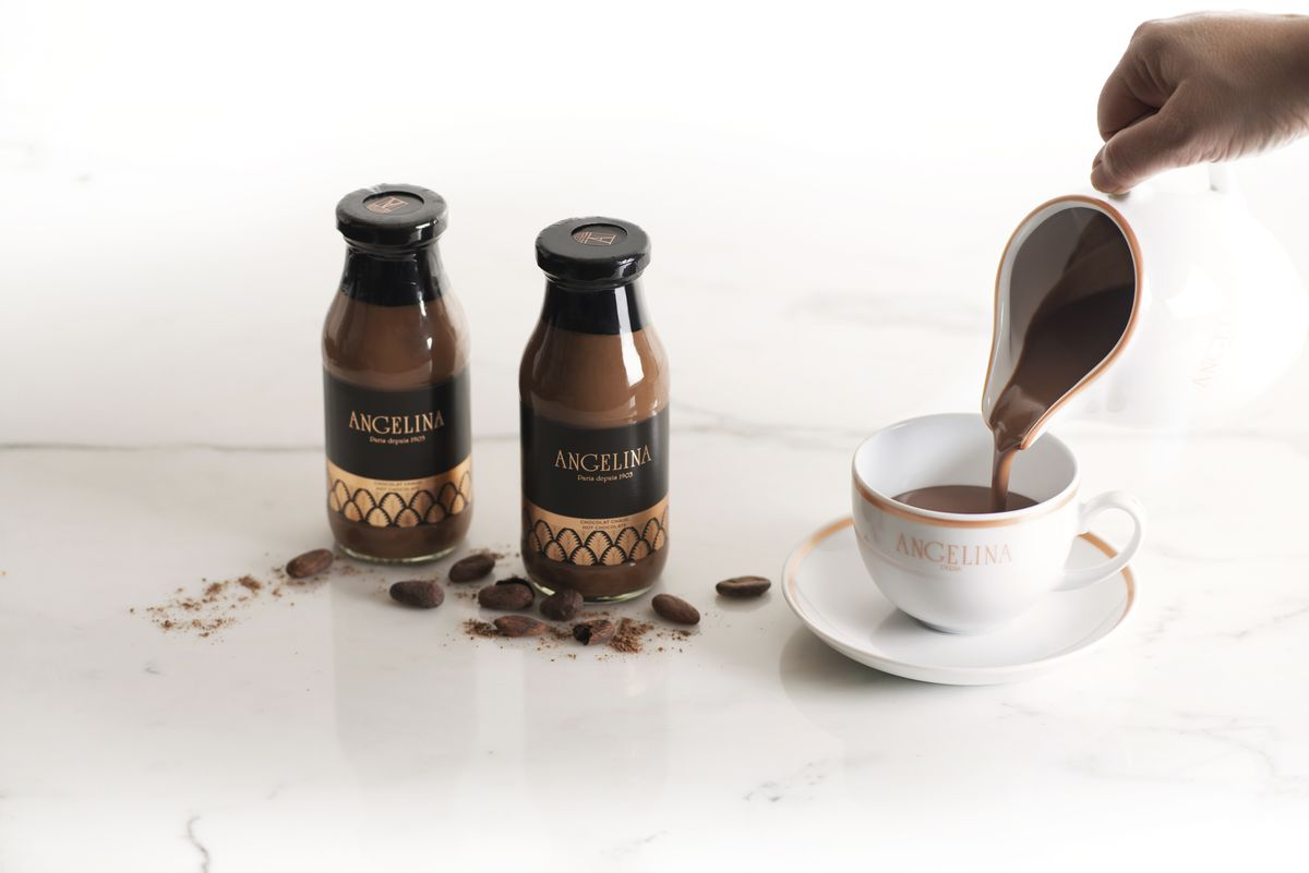 Two bottles of hot chocolate sit on a marble countertop along with a cup that hot chocolate is being poured into