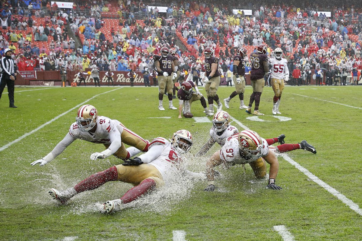 San Francisco 49ers defensive end Arik Armstead, defensive tackle DeForest Buckner, defensive end Nick Bosa, and middle linebacker Kwon Alexander celebrate by sliding on the wet field after the final play at FedExField.