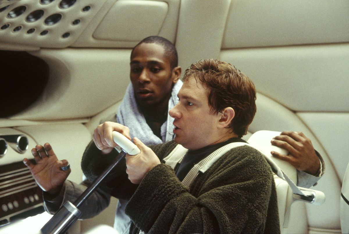 Yasiin Bey and Martin Freeman at the wheel of a spaceship in The Hitchhiker's Guide to the Galaxy