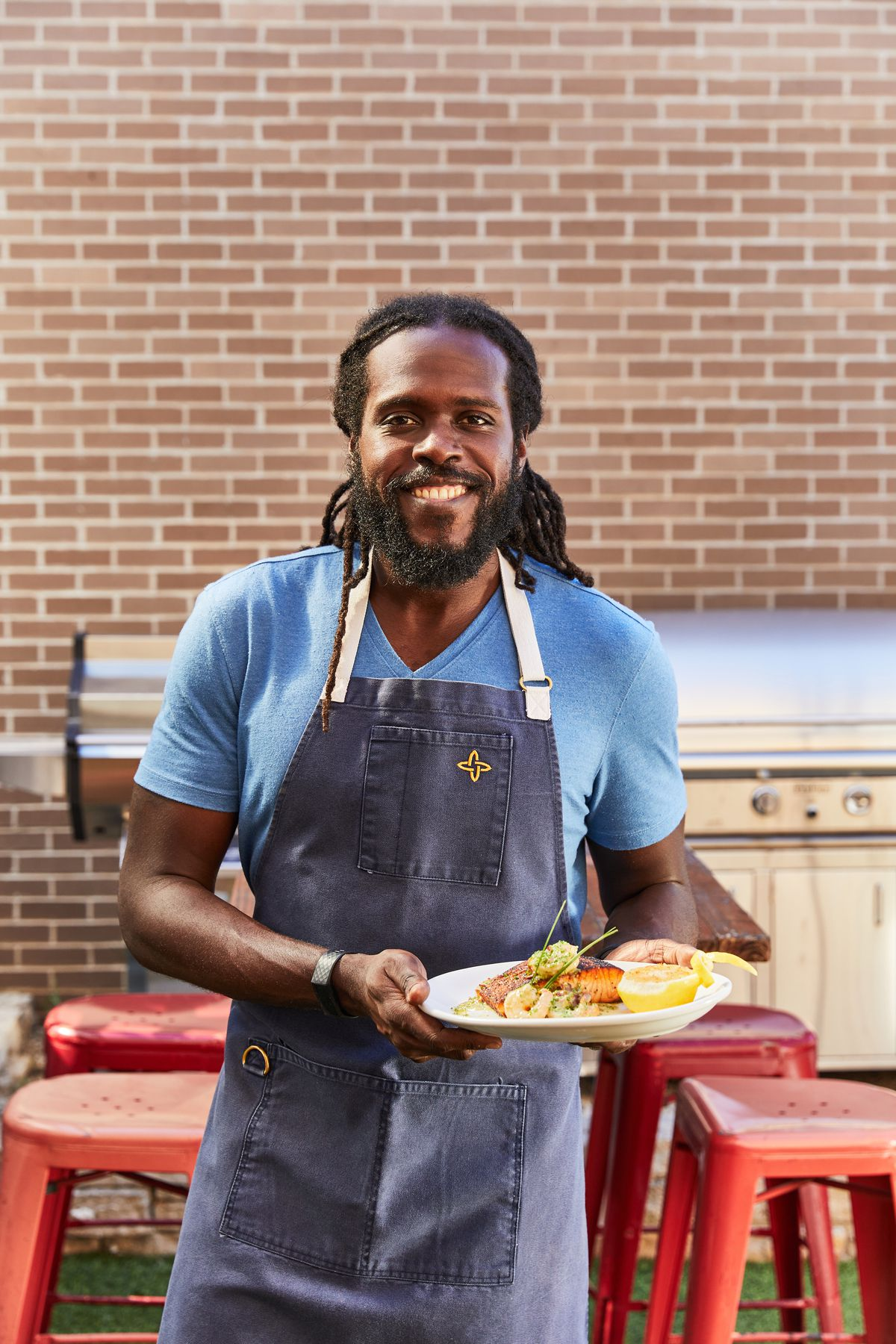 A smiling and standing man holding a plate of food