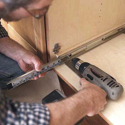 Man Mounts Slides Of Pull Out Kitchen Cabinet Shelves