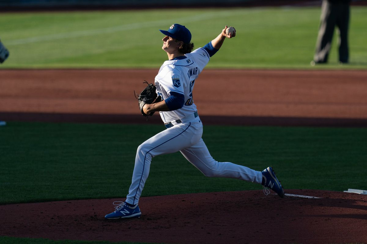 A pitcher in mid-delivery, throwing toward the left side of the picture. His bottom half is in dark shadows, but his upper half and face are in bright sun. His uniform top and pants are both white, with a blue cap.