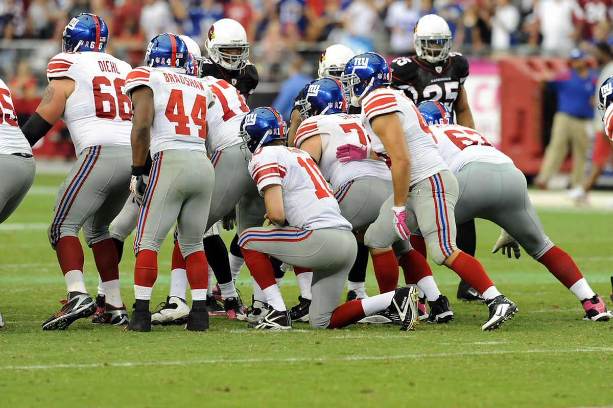 Eli Manning (10) of the New York Giants takes a knee to run out the clock as the Giants beat the Cardinals 31-27 at University of Phoenix Stadium on October 2, 2011 in Glendale, Arizona.  (Photo by Norm Hall/Getty Images)
