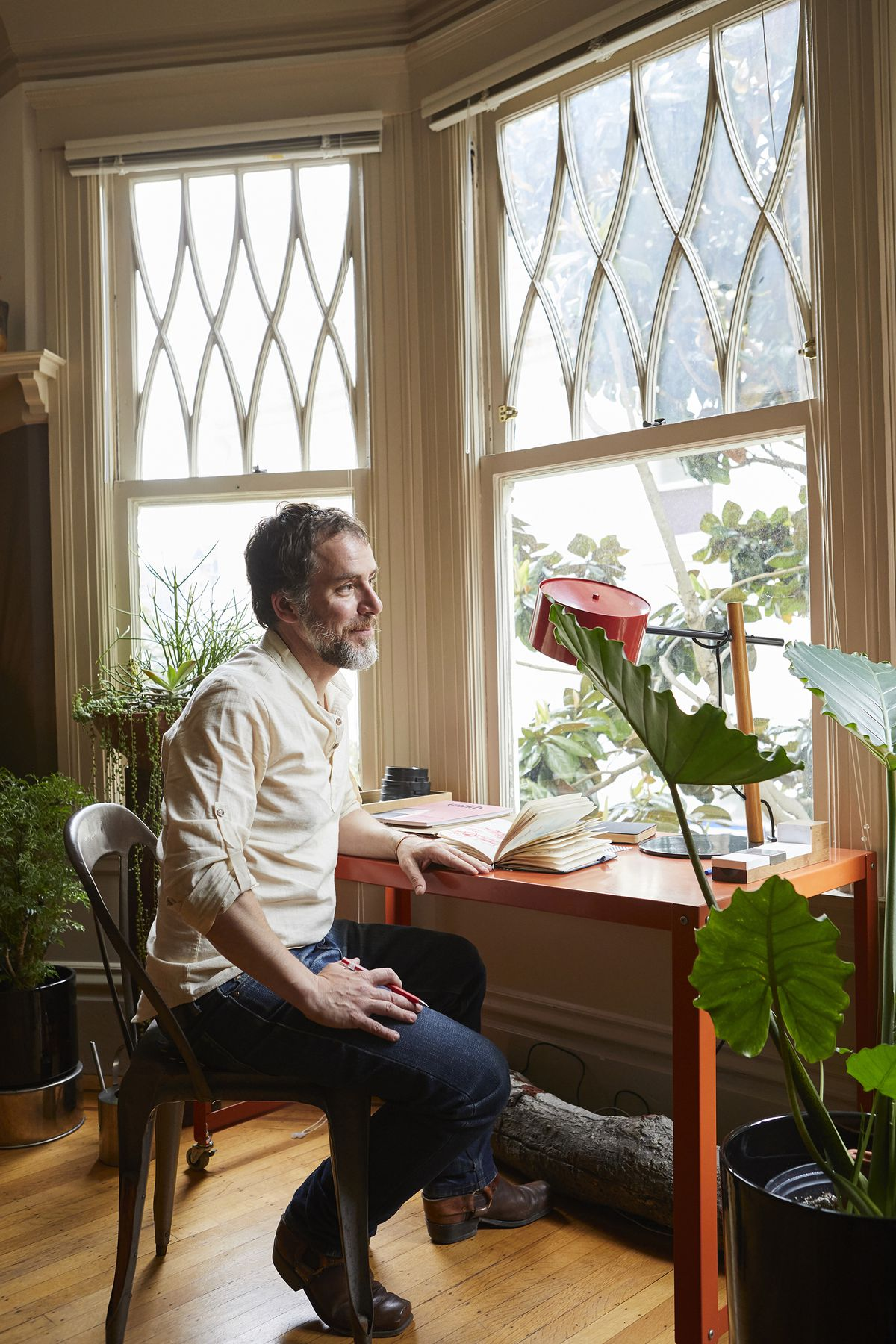 A man sits in a chair in front of a red table that has an open book and a red lamp. The man is leaning on the table while looking out the window in front of the desk. There is a houseplant in the foreground.