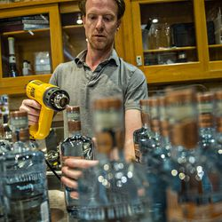 Jeff Moore uses a heat gun to seal bottles of vodka during bottling day at Old 4th Distillery.