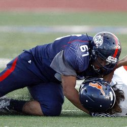 Mountain Crest's #5 Jamison Webb, right, is brought down by Woods Cross' #61 Delon Saumalu as Woods Cross and Mountain Crest play Friday, Aug. 31, 2012.
