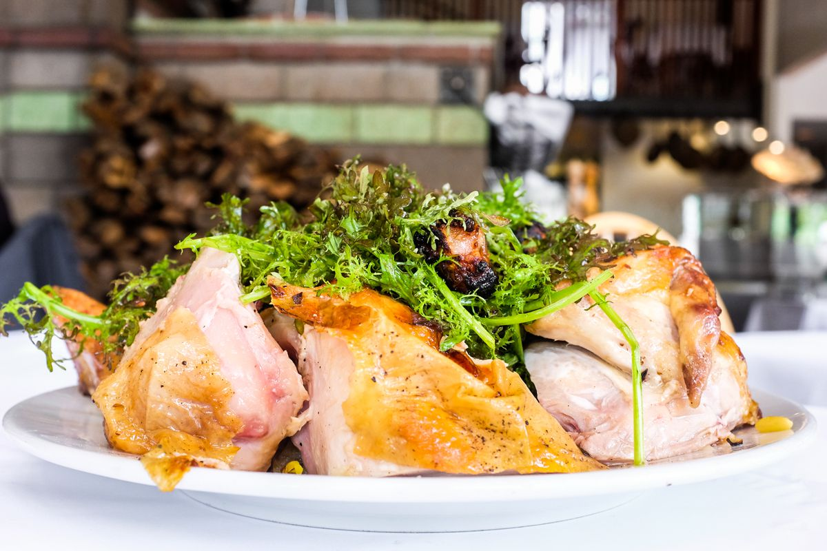 Cut-up pieces of roasted chicken with arugula on top.