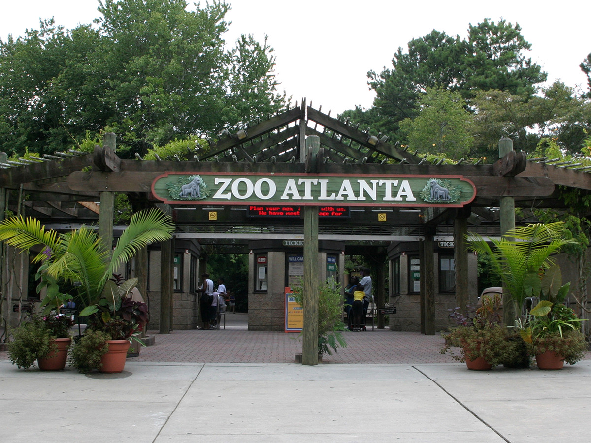 A building surrounded by trees. There is a sign on the building that reads: Zoo Atlanta.