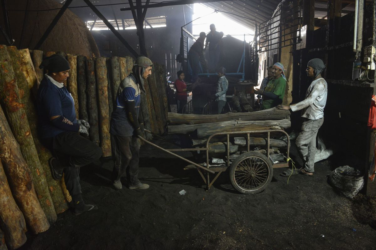 Foreign workers take a rest after carrying out the charcoal from the stove in a factory outside Kuala Lumpur, Malaysia.