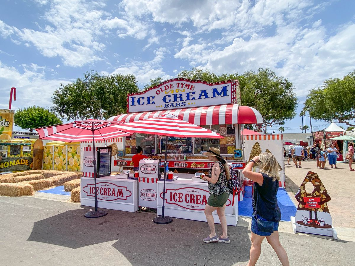 A side-angle view of a working ice cream stand at a county fair.