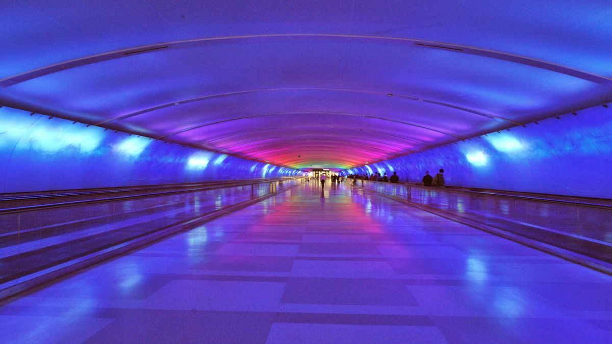 A tunnel walkway in Detroit Metro Airport. The walkway's walls and ceiling are various shades of purple.